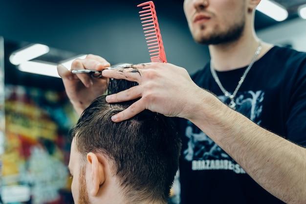 Coiffeur homme coupe les cheveux d'un client