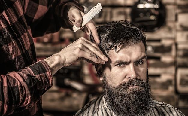 Coiffeur homme homme barbu dans un salon de coiffure coiffeur au service du client au salon de coiffure barbu
