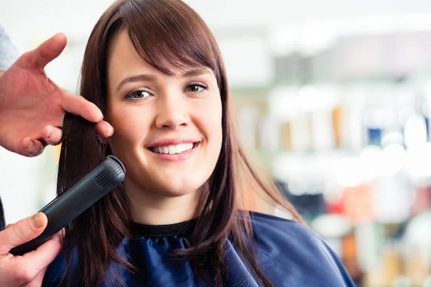 Coiffeur homme robe femme cheveux avec fer plat dans magasin