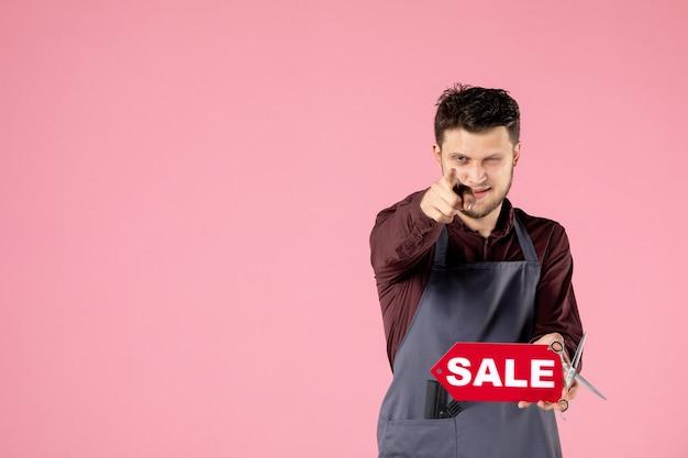 Coiffeur homme vue de face avec plaque signalétique de vente rouge sur fond rose
