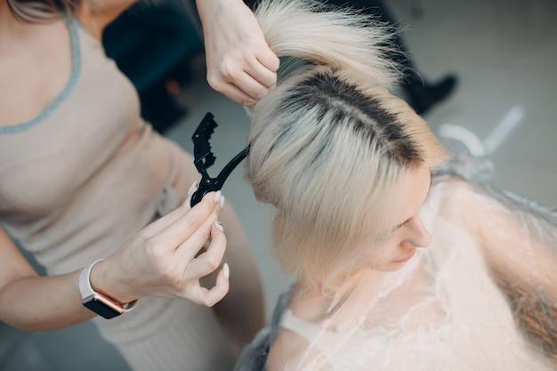 Coiffeur de jeune femme avec des cheveux mourants de broche au salon de beauté. coloration professionnelle des racines des cheveux