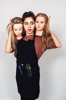 Le coiffeur de la jeune fille tient en mains deux têtes de mannequin.