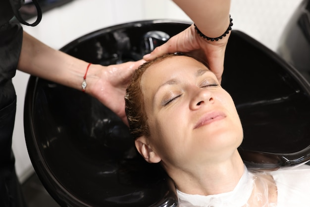 Coiffeur lavant les cheveux d'un client