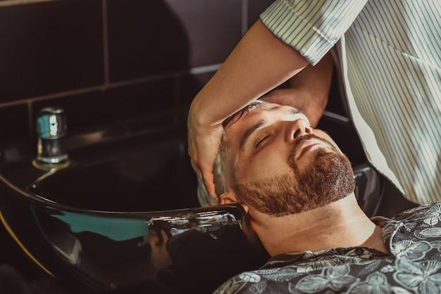 Le coiffeur lave les cheveux d'un homme barbu avant une coupe de cheveux