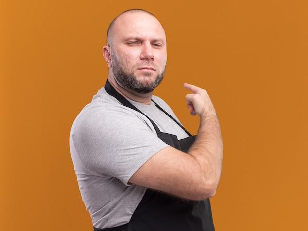 Un coiffeur masculin d'âge moyen confiant en uniforme pointe derrière isolé sur un mur orange avec espace pour copie