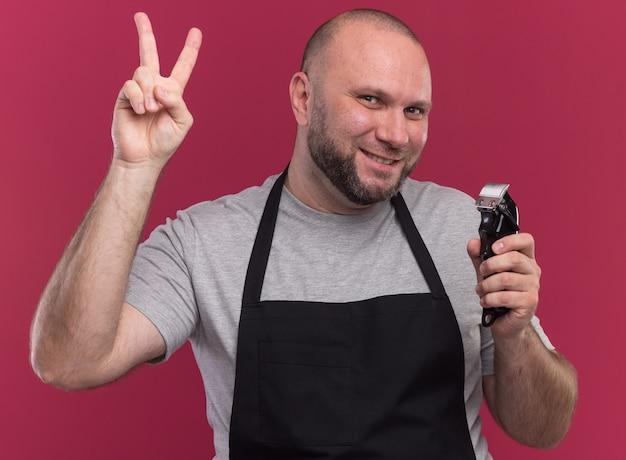 Coiffeur masculin d'âge moyen souriant en uniforme tenant une tondeuse à cheveux montrant un geste de paix isolé sur un mur rose