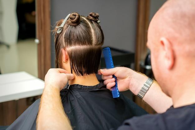 Coiffeur masculin coupe les cheveux de la jeune femme tenant un peigne au salon de coiffure.
