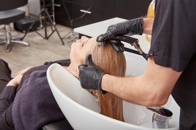 Coiffeur masculin lavant les cheveux du client dans l'évier