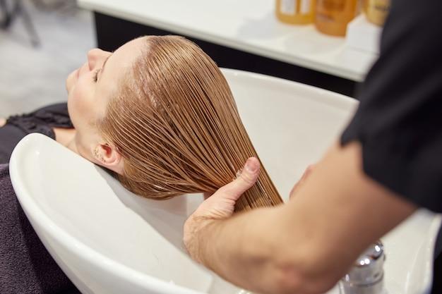 Coiffeur masculin laver les cheveux du client dans un salon de coiffure