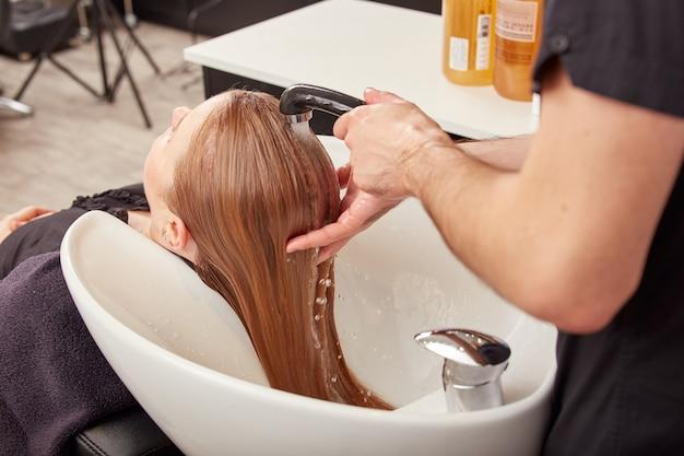Coiffeur masculin laver les cheveux de la jeune femme dans l'évier