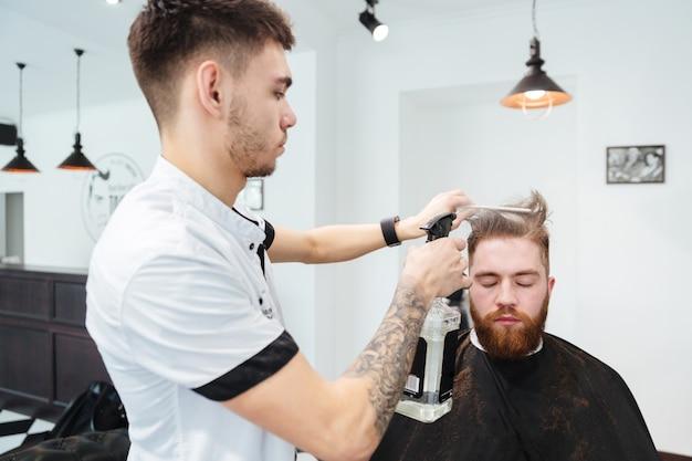 Coiffeur masculin peignant les cheveux d'un client masculin au salon de coiffure