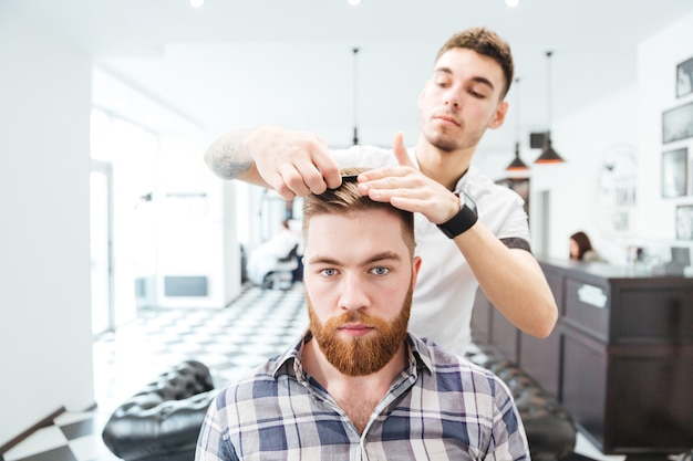 Coiffeur masculin peignant les cheveux à son client dans le salon de coiffure