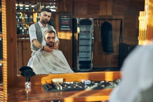 Coiffeur masculin qualifié fixant une cape autour du cou de son client avant de se mettre à travailler sur ses cheveux