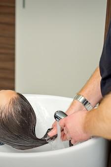 Coiffeur masculin rince les cheveux de la jeune femme dans un salon de coiffure