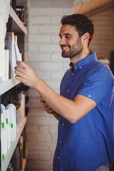 Coiffeur masculin sélectionnant le shampooing de l'étagère
