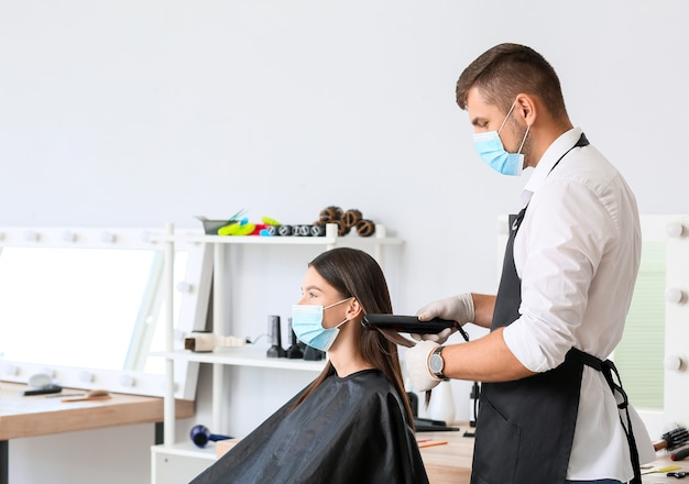 Coiffeur masculin travaillant avec un client dans un salon pendant l'épidémie de coronavirus
