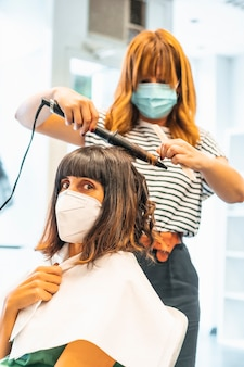 Coiffeur avec masque et client, commençant la coiffure ondulée. réouverture avec des mesures de sécurité pour les coiffeurs dans la pandémie de covid-19. nouvelle normale, coronavirus, distance sociale