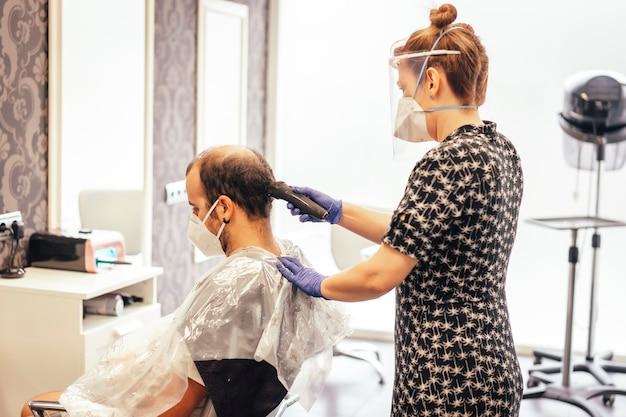Coiffeur avec mesures de sécurité pour le covid-19, nouvelle normalité, distance sociale, coiffeur coupe les cheveux avec masque et écran de protection en plastique