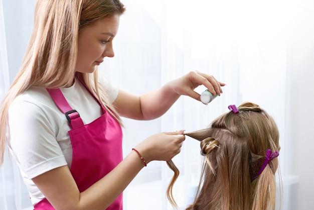Le coiffeur met de la poudre pour le volume sur les cheveux du client