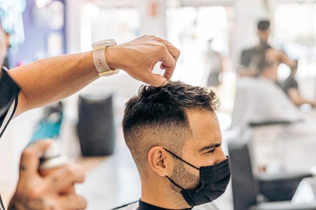 Coiffeur mettant de la laque sur les cheveux d'un homme de race blanche portant un masque dans un salon de coiffure