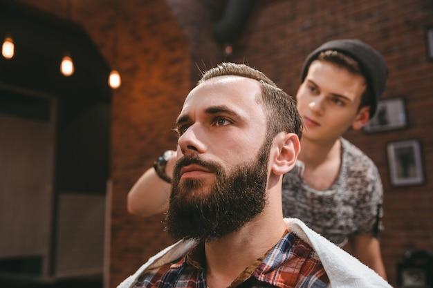 Coiffeur moderne au chapeau noir peignant les cheveux du client avec la barbe au salon de coiffure