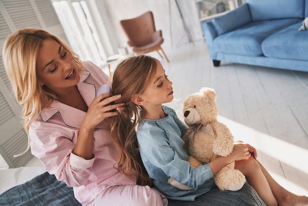 Coiffeur parfait. vue de dessus de la belle jeune mère se brosser les cheveux de sa fille assise sur le lit à la maison