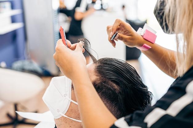 Coiffeur peignant les cheveux d'un homme se faisant couper les cheveux dans un salon de coiffure avec une petite brosse
