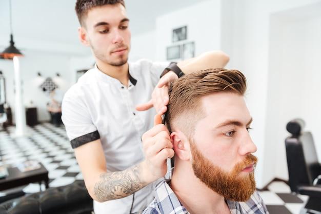 Coiffeur peignant les cheveux à son client dans un salon de coiffure