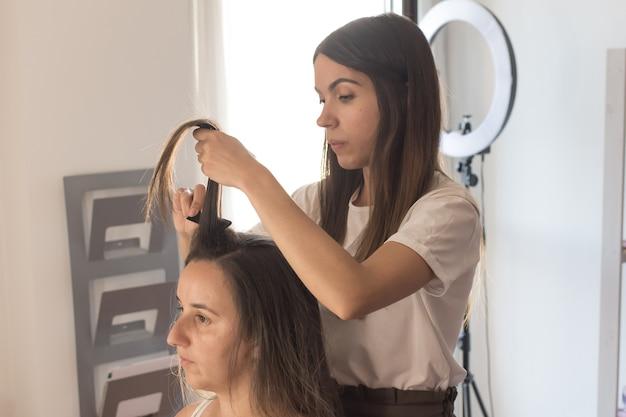 Coiffeur peignant, coupant et lissant les cheveux du client. séance de coiffure.