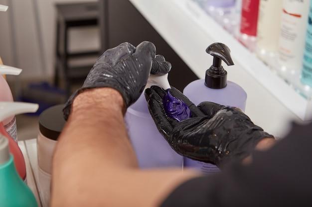 Coiffeur pompant le shampooing violet blond de la bouteille