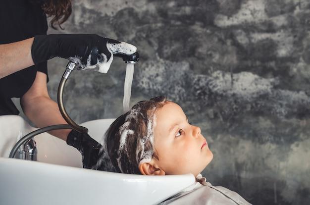 Coiffeur Portant Des Gants En Latex Noir Rincer Les Cheveux D'un Enfant Après Le Lavage Photo Premium