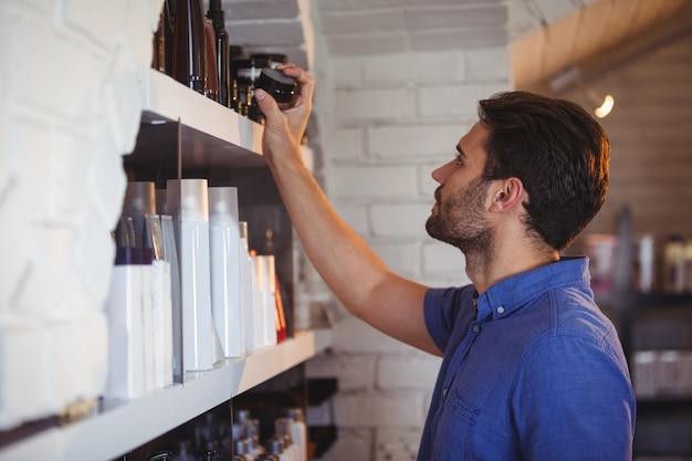 Coiffeur pour hommes sélectionnant le gel de l'étagère