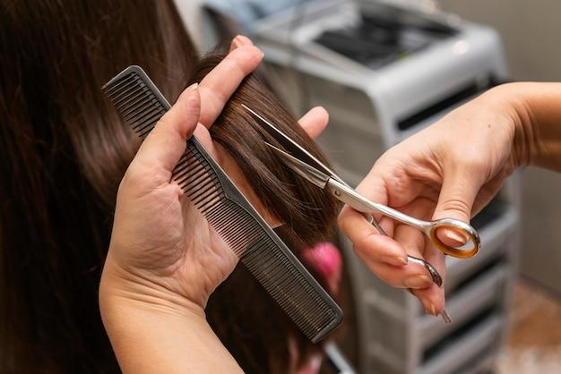Coiffeur prenant soin des cheveux d'un client au salon
