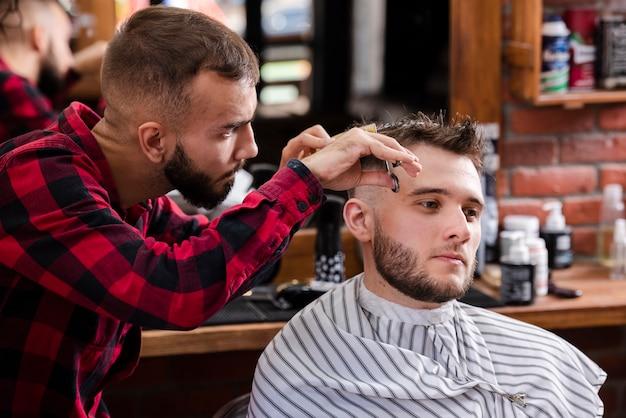 Coiffeur prenant soin des cheveux d'un client