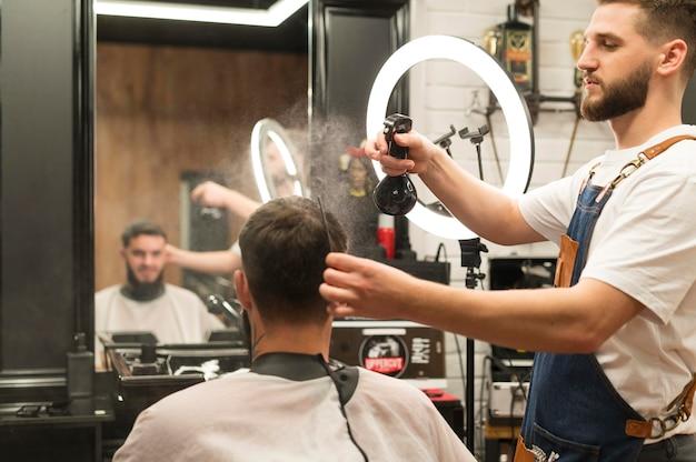 Coiffeur préparant les cheveux du client masculin pour la coupe