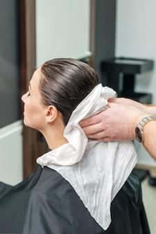 Coiffeur professionnel essuyant les cheveux de son client