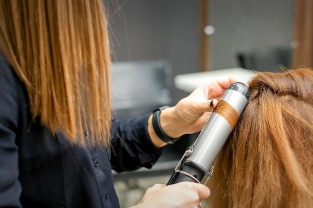 Coiffeur professionnel fait des boucles avec un fer à friser pour une jeune femme aux longs cheveux roux dans un salon de beauté