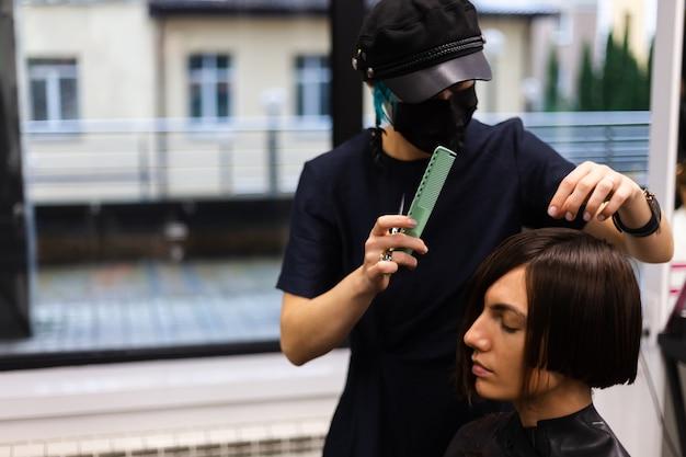 Un coiffeur professionnel fait une coupe de cheveux à un client. la jeune fille est assise dans un masque de beauté le salon