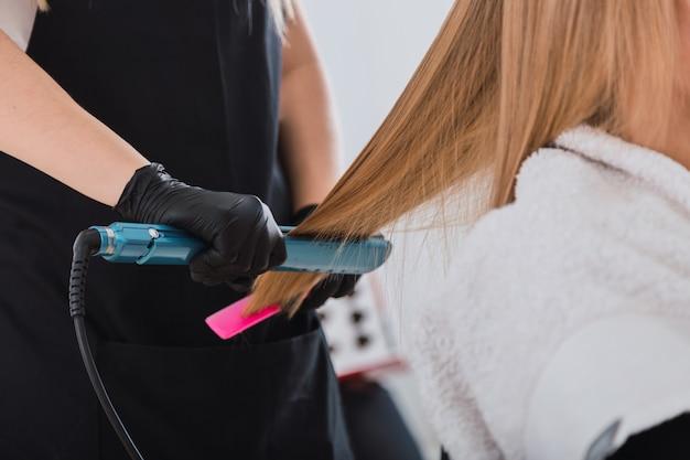 Coiffeur professionnel lissant les cheveux du client.