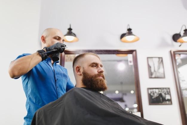 Coiffeur professionnel masculin servant le client par des ciseaux