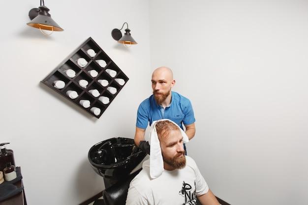 Coiffeur professionnel masculin servant la tête de lavage du client dans un lavabo à la mode noir, essuyant avec une serviette