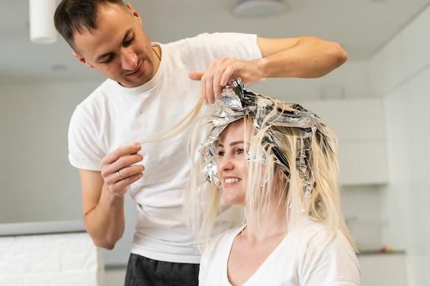 Coiffeur professionnel masculin teint les cheveux femme au salon
