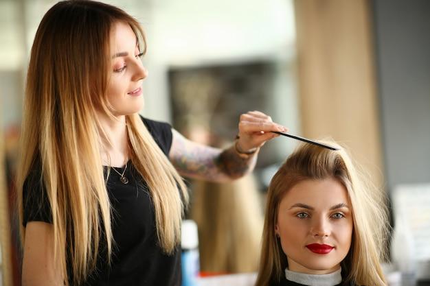 Coiffeur professionnel peignant les cheveux de client de fille