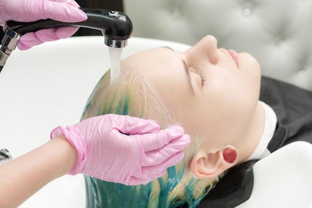 Le coiffeur professionnel d'un salon de coiffure lave la tête des clients avec des cheveux verts.