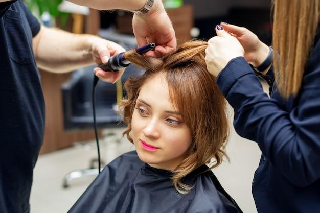 Coiffeur professionnel tord les boucles de longs cheveux brun clair de femme avec un fer à friser dans un salon de beauté. procédures de coiffure