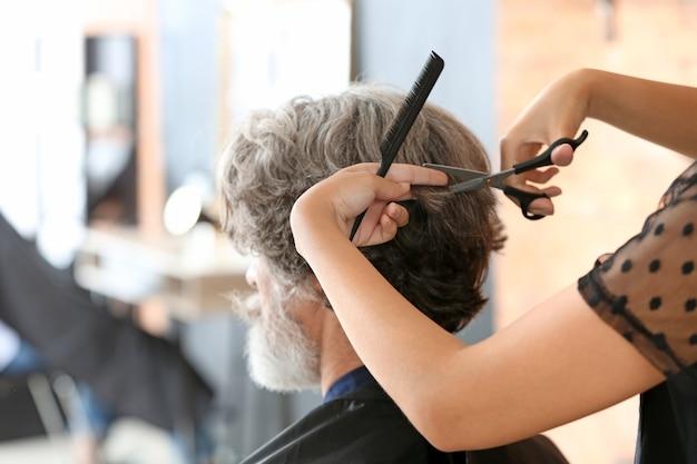 Coiffeur professionnel travaillant avec le client dans un salon de beauté