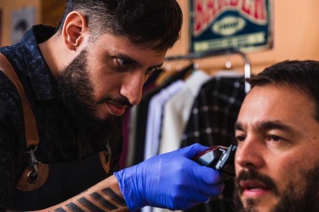 Coiffeur qui s'occupe du client dans le salon de coiffure