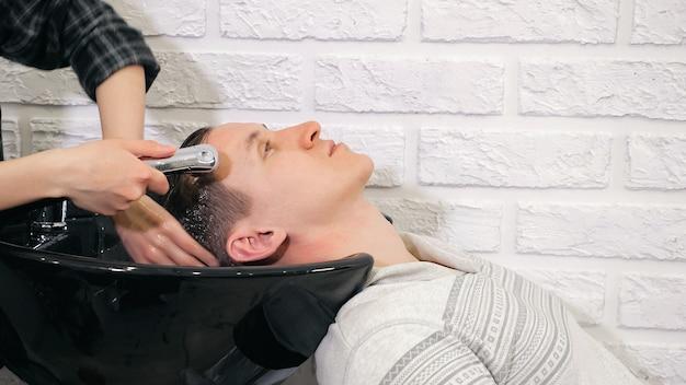 Le coiffeur de salon de coiffure lave la tête d'un homme