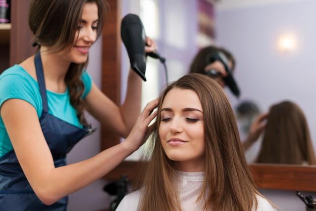 Coiffeur séchant les cheveux de la femme
