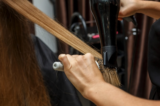 Le coiffeur sèche les cheveux au client avec un sèche-cheveux.